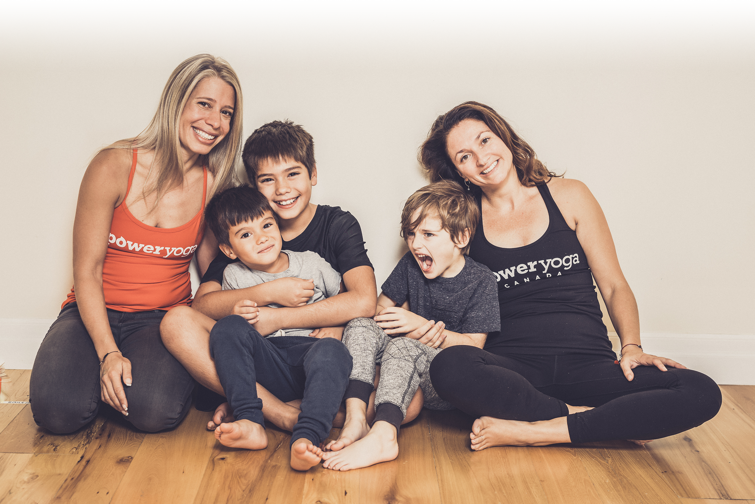 Yoga instructors (Pauline and Kin) wearing Power Yoga Canada tank-tops posing with kids